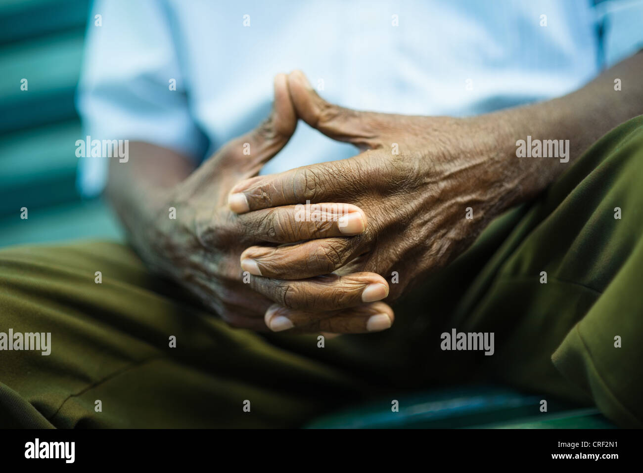 closeup of hands of elderly african american man sitting on bench - Stock Image