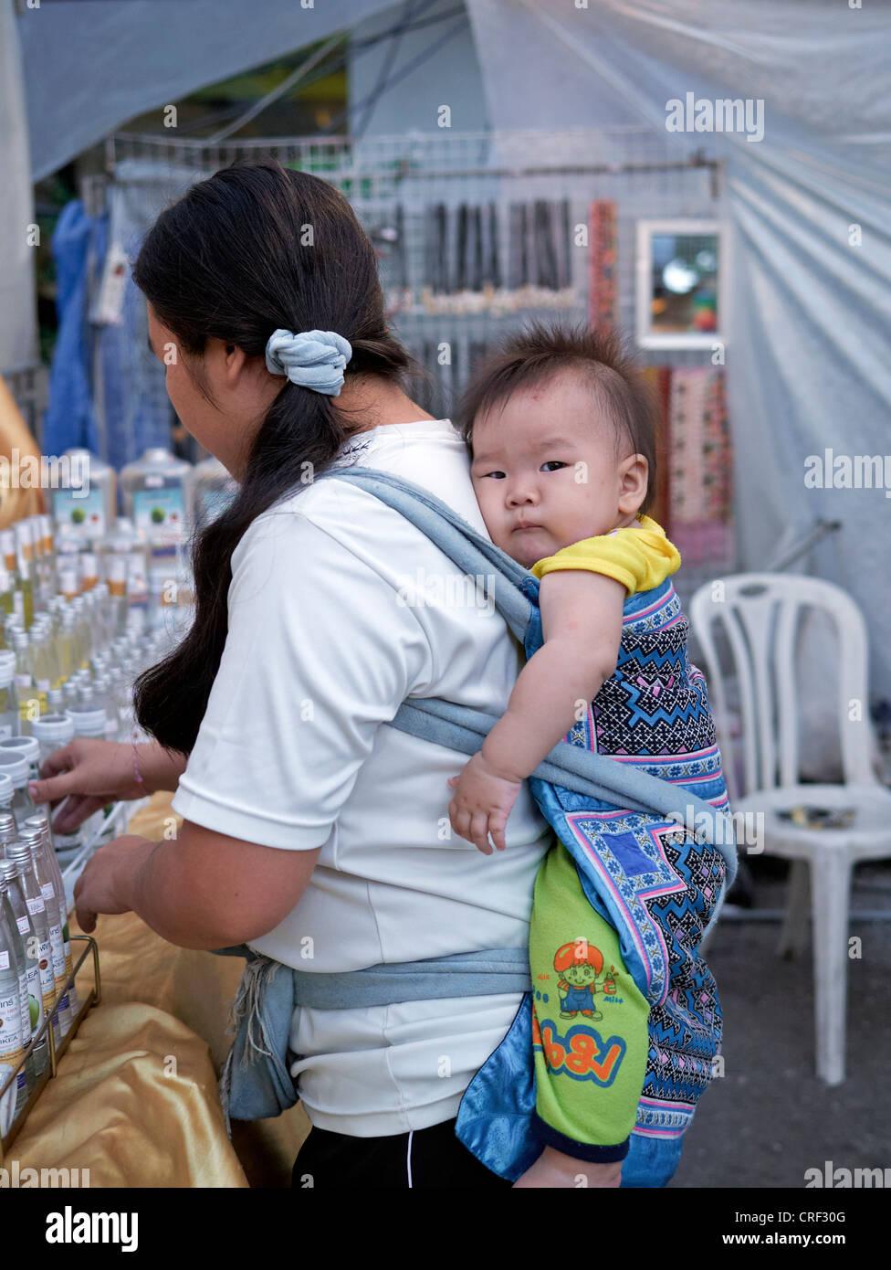 bce4ea1bffd Child back sling. Female Thai market stall holder carrying baby on her back.  Thailand
