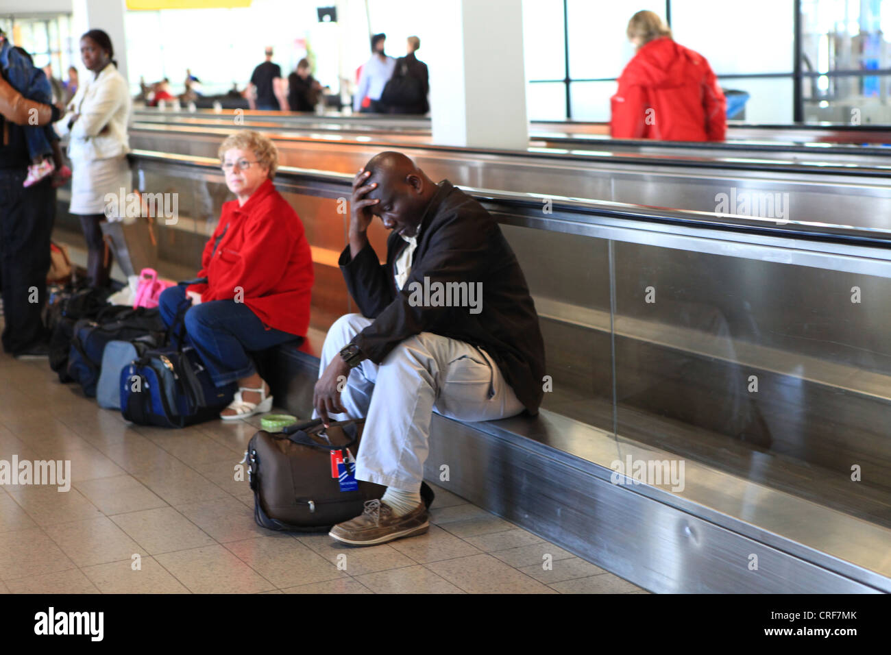 Tired male traveller waiting for connection flight at Frankfurt airport - Stock Image