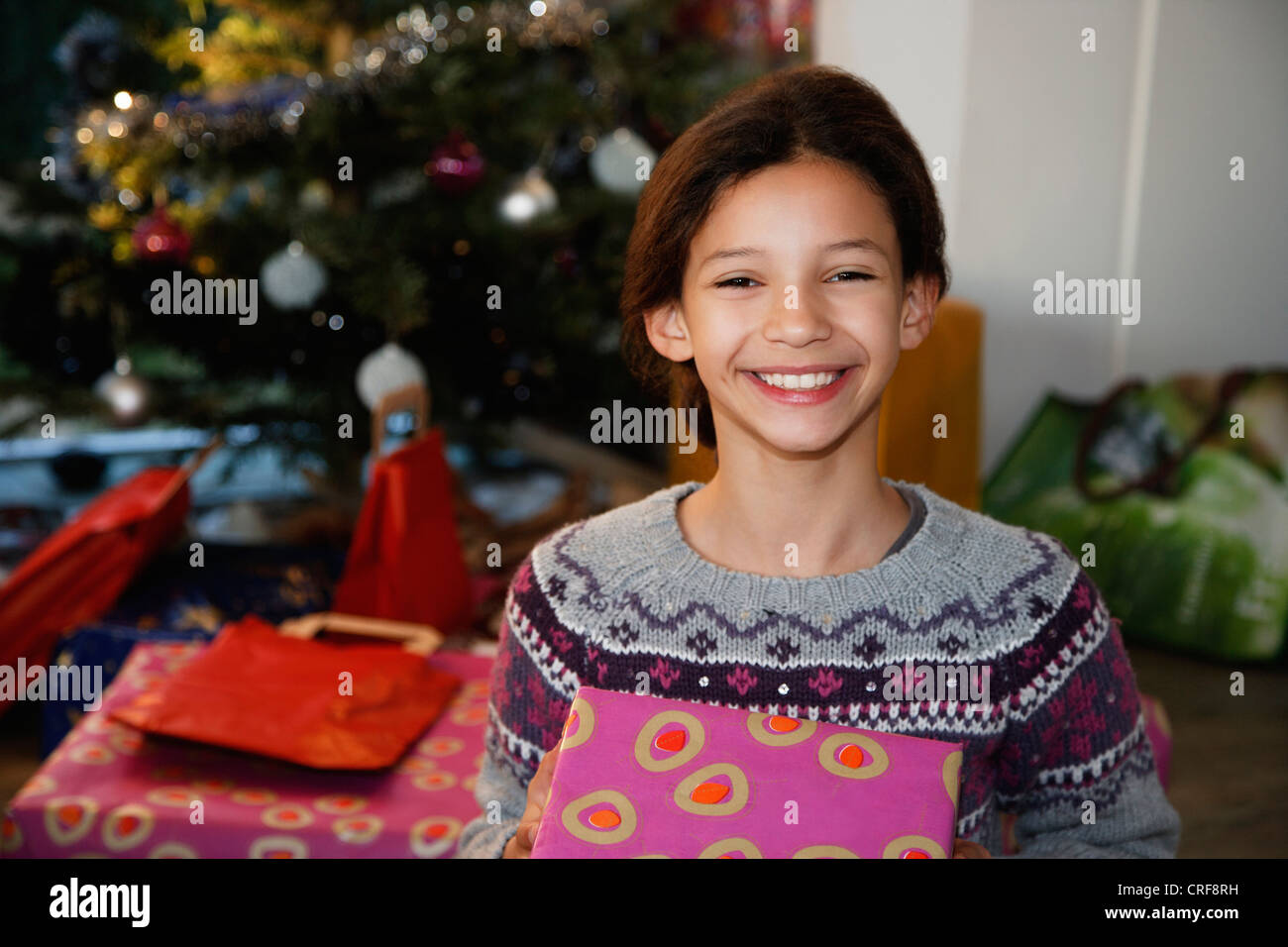 Smiling girl holding Christmas present - Stock Image