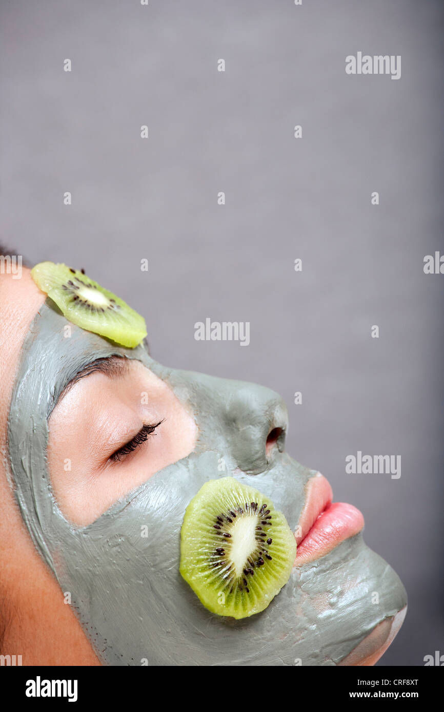 Woman with skin mask and kiwi in bath - Stock Image