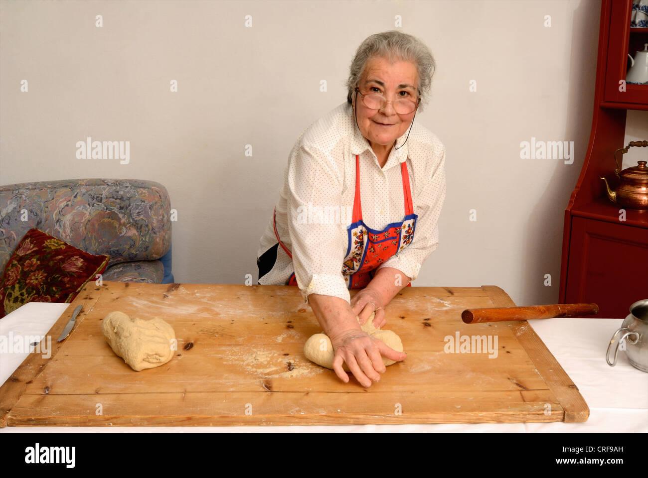 Older woman kneading dough on board Stock Photo