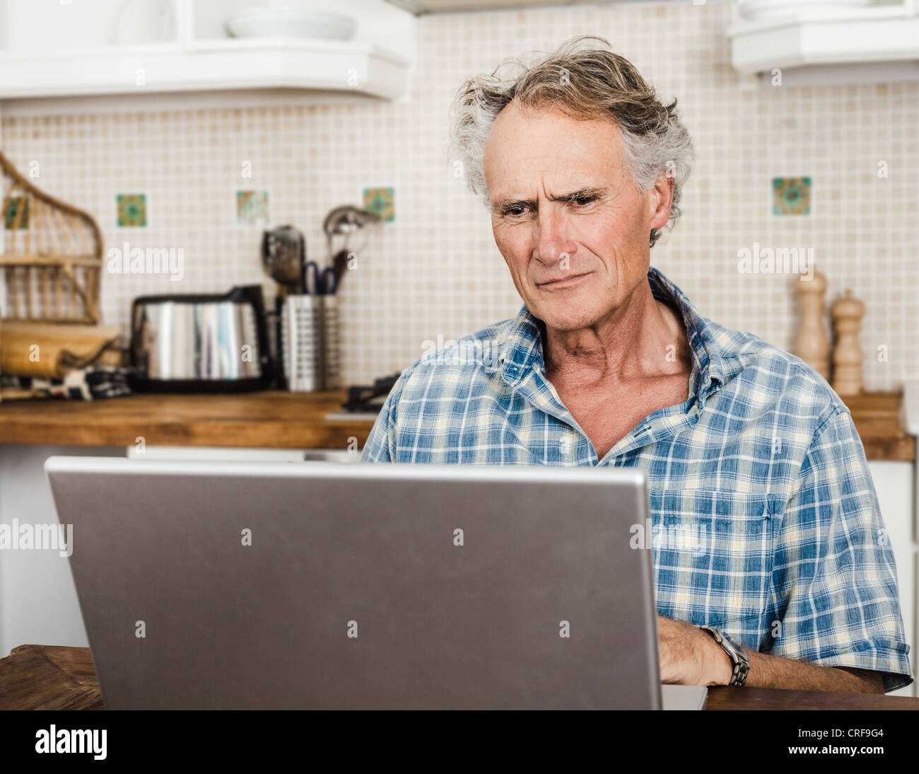 Older man using laptop in kitchen - Stock Image