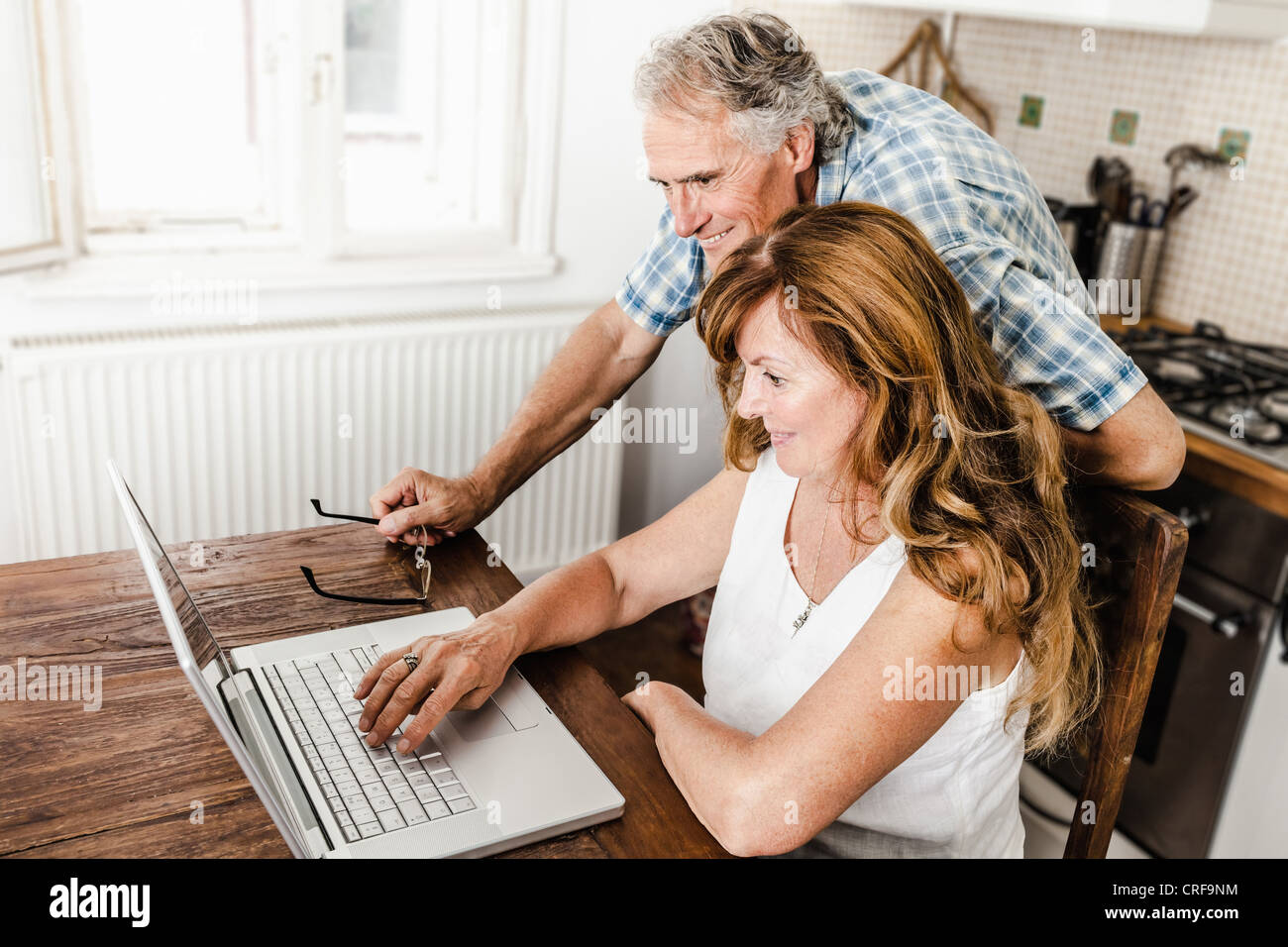 Older couple using laptop in kitchen - Stock Image