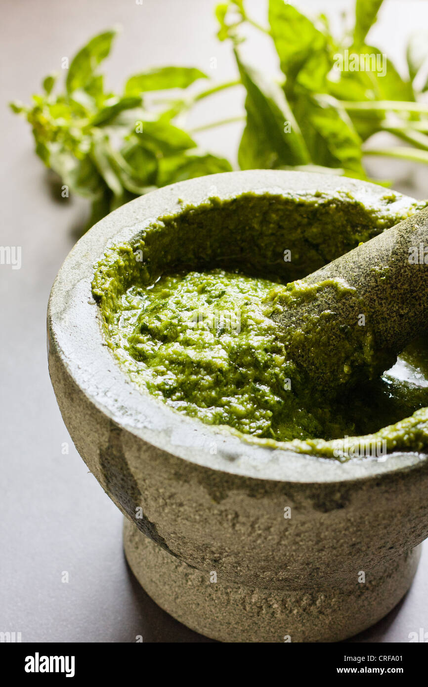 Homemade Pesto in mortar and pestle and basil leaves on yhe background - Stock Image