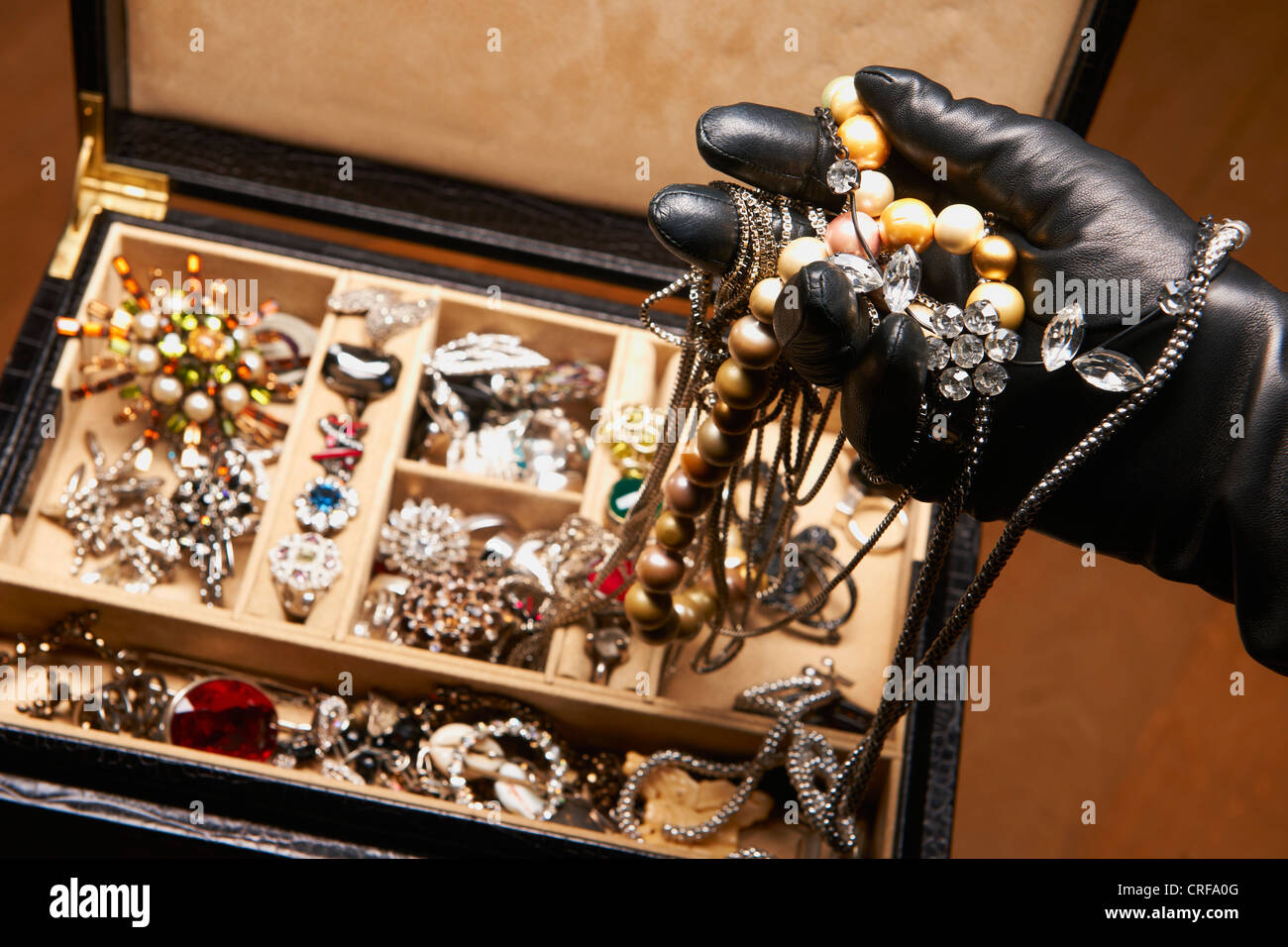 Gloved hand stealing jewelry - Stock Image