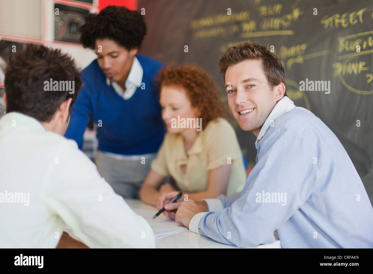 Businessman smiling in meeting - Stock Image