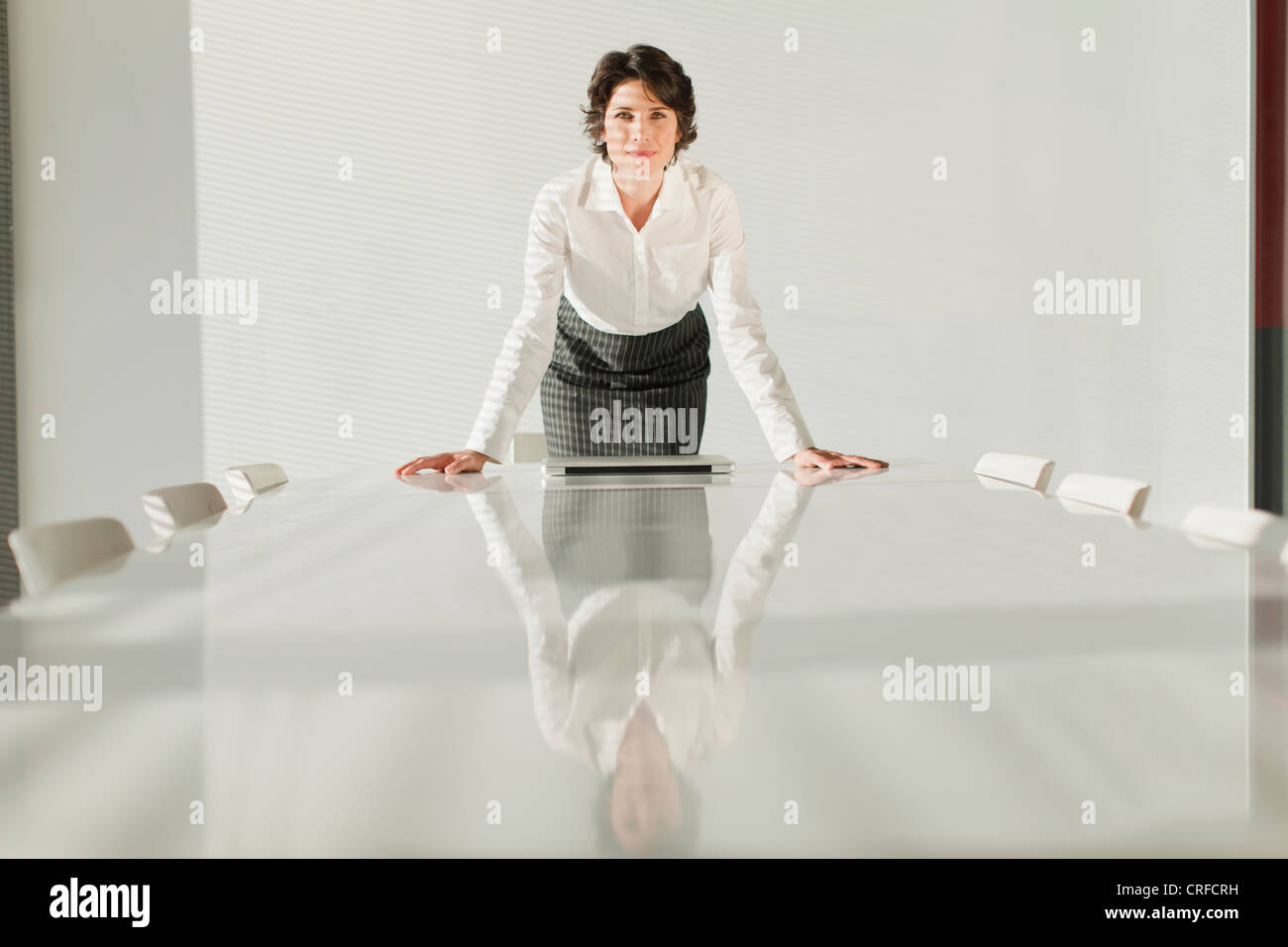 Businesswoman reflected in table - Stock Image