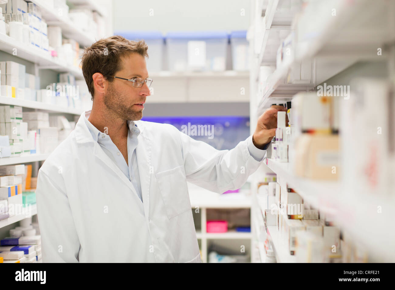 Pharmacist browsing medicines on shelf - Stock Image