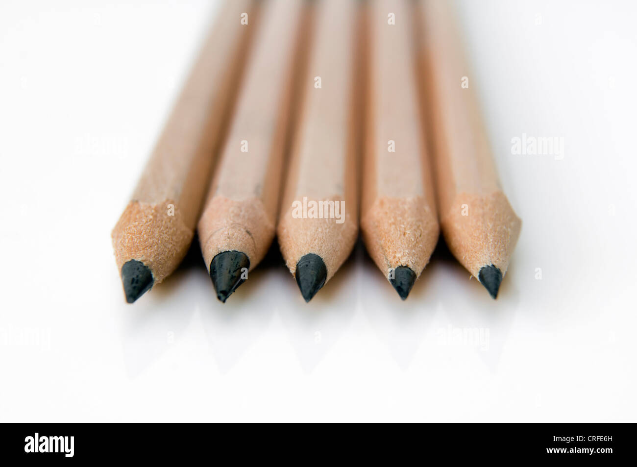Five sharpened black HB pencils on white background - Stock Image
