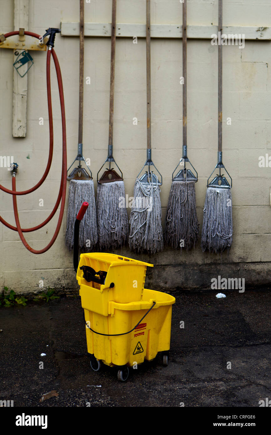 5 Mops hanging on a wall behind a mop bucket - Stock Image