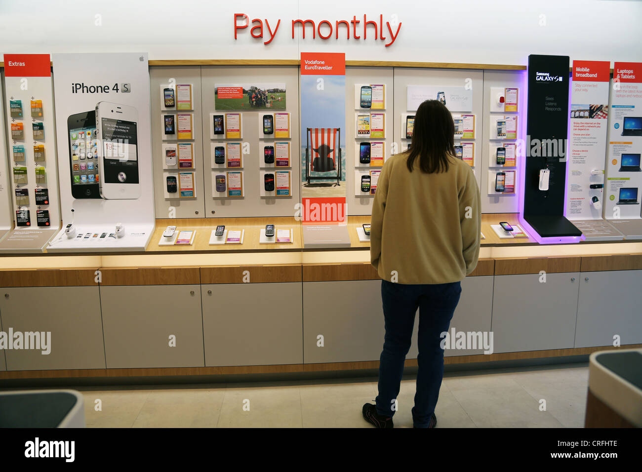 0b1802ed44f Customer Looking At Monthly Contract Mobile Phones In Vodaphone Shop Surrey  England