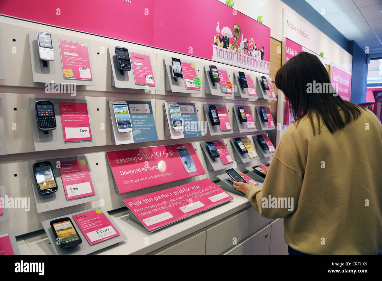 3261f1e24c7 Customers Looking At Phones in Mobile Phone Shop Surrey England ...