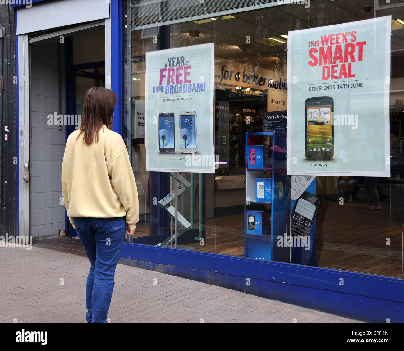 a58bf4a6a0f Woman Looking At Mobile Phones Advertised In Mobile Phone Shop Window Surrey  England