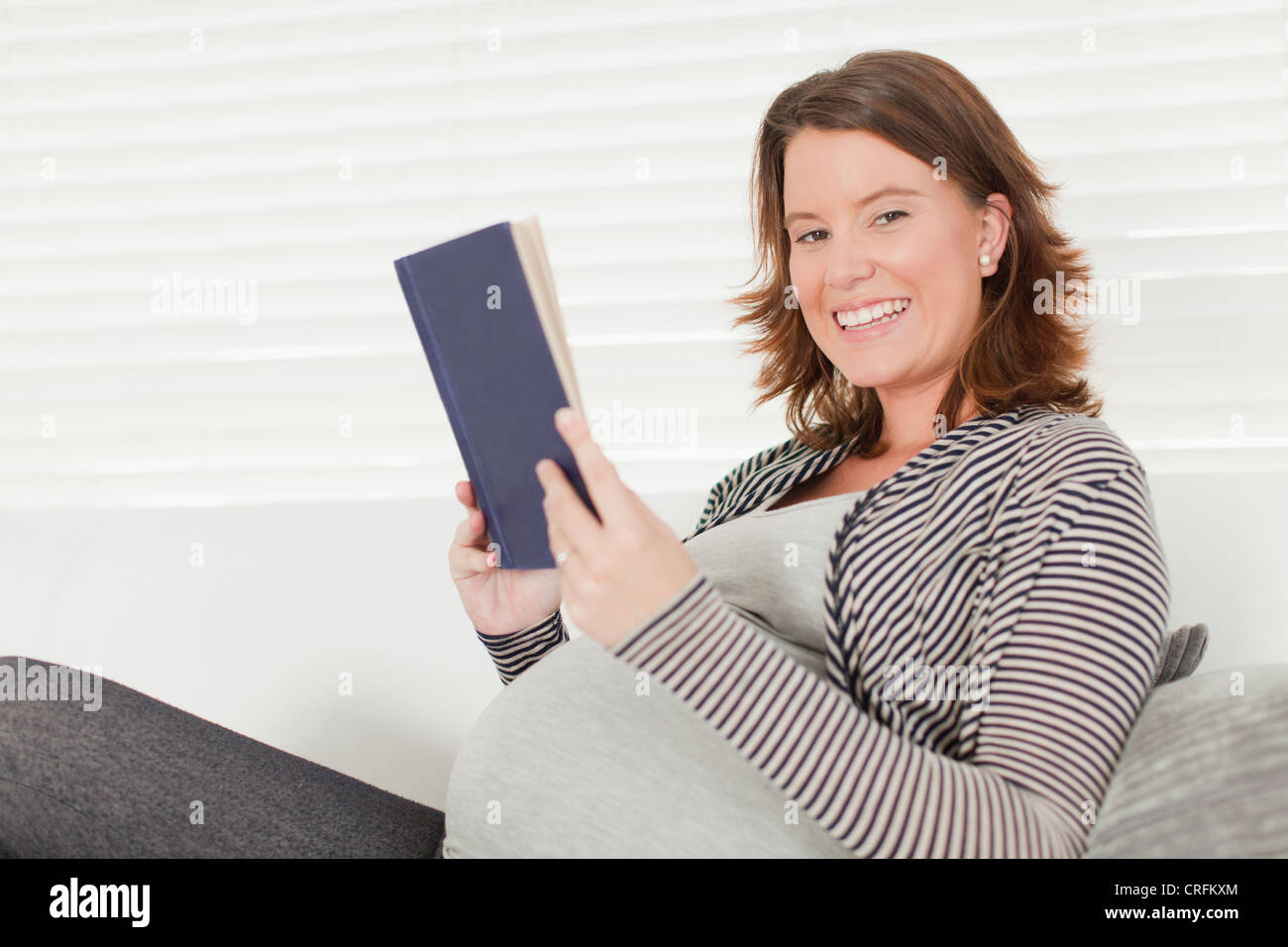 Pregnant woman reading book on sofa - Stock Image
