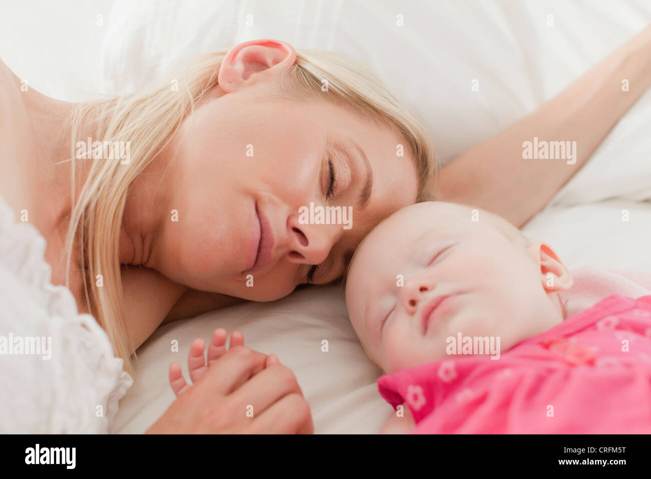Mother and baby sleeping on bed - Stock Image