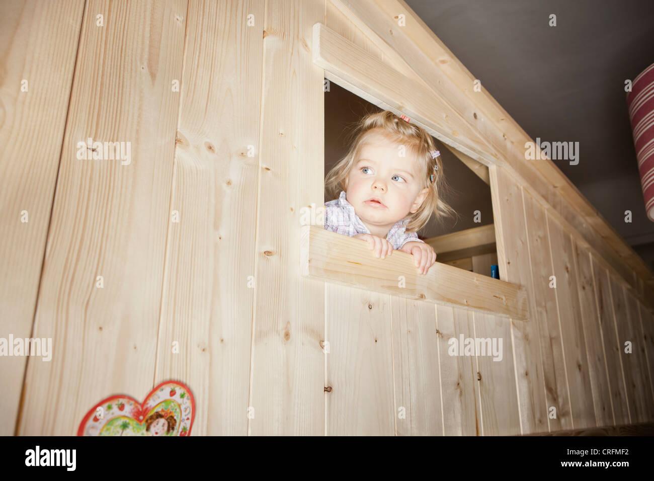 Girl peeking out window of playhouse - Stock Image