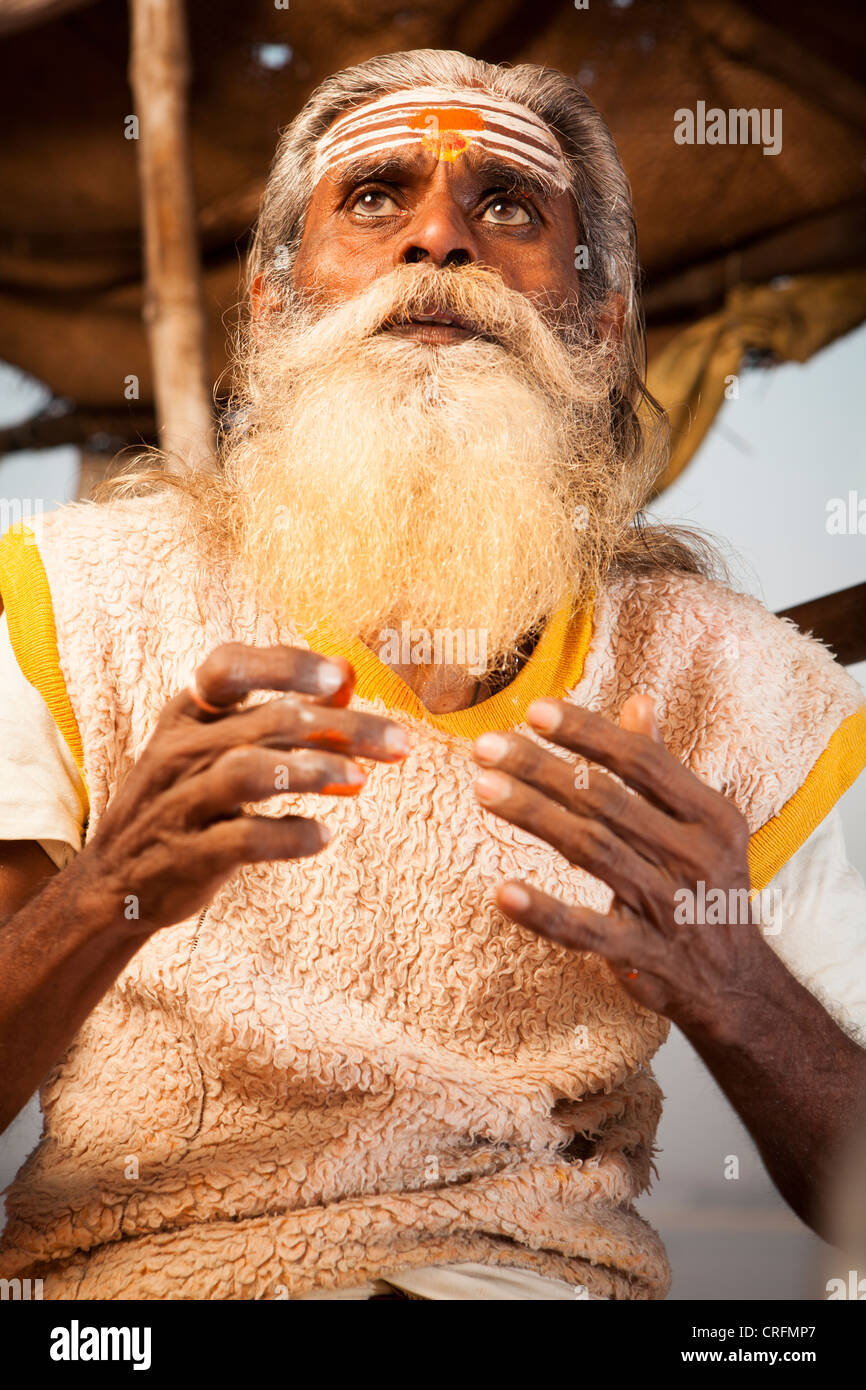Hindu monk Sadhu show me , how to decorating himself for god, Varanasi, Uttar Pradesh, India - Stock Image