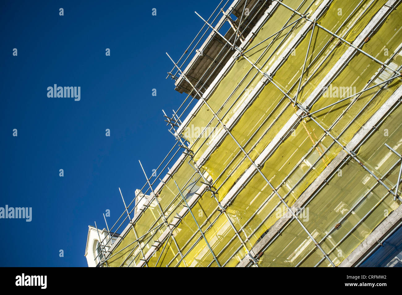 Netting covered scaffolding on the exterior of a building being renovated, UK - Stock Image