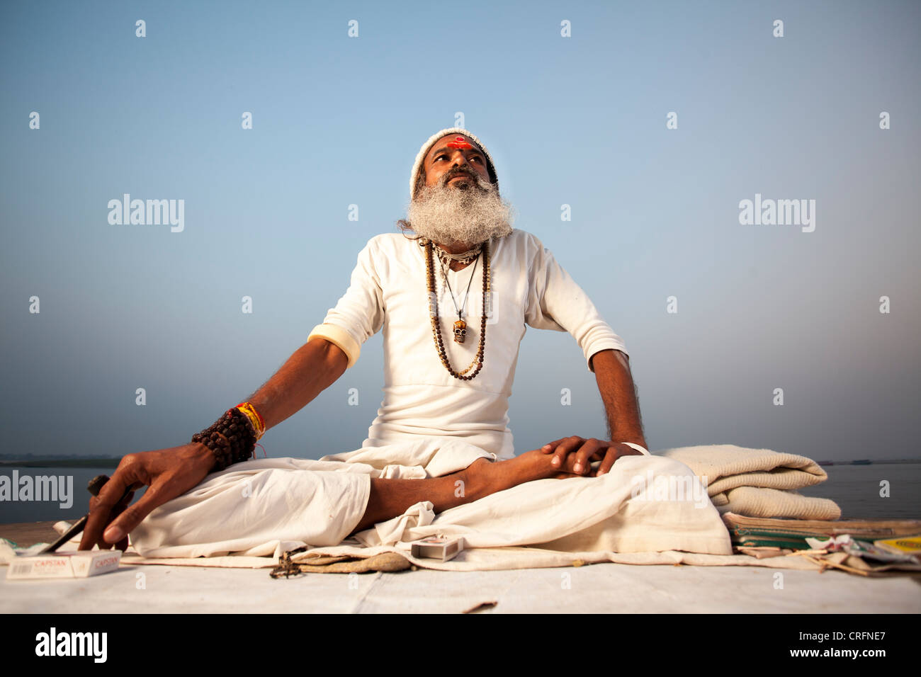 Hindu monk Sadhu(as holy man) sit on the Ghat in Varanasi, Uttar Pradesh, India - Stock Image
