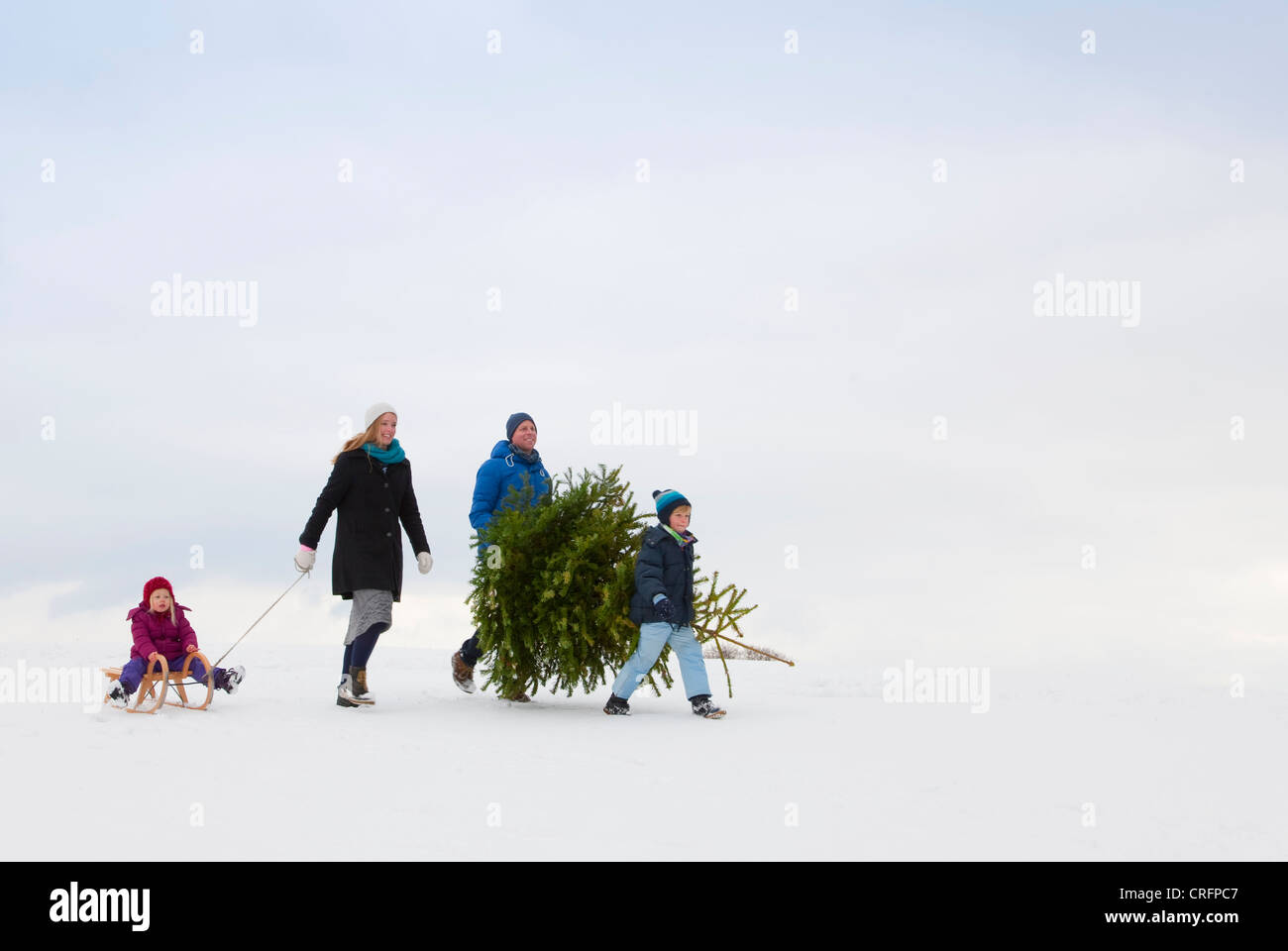 Family walking together in snow - Stock Image