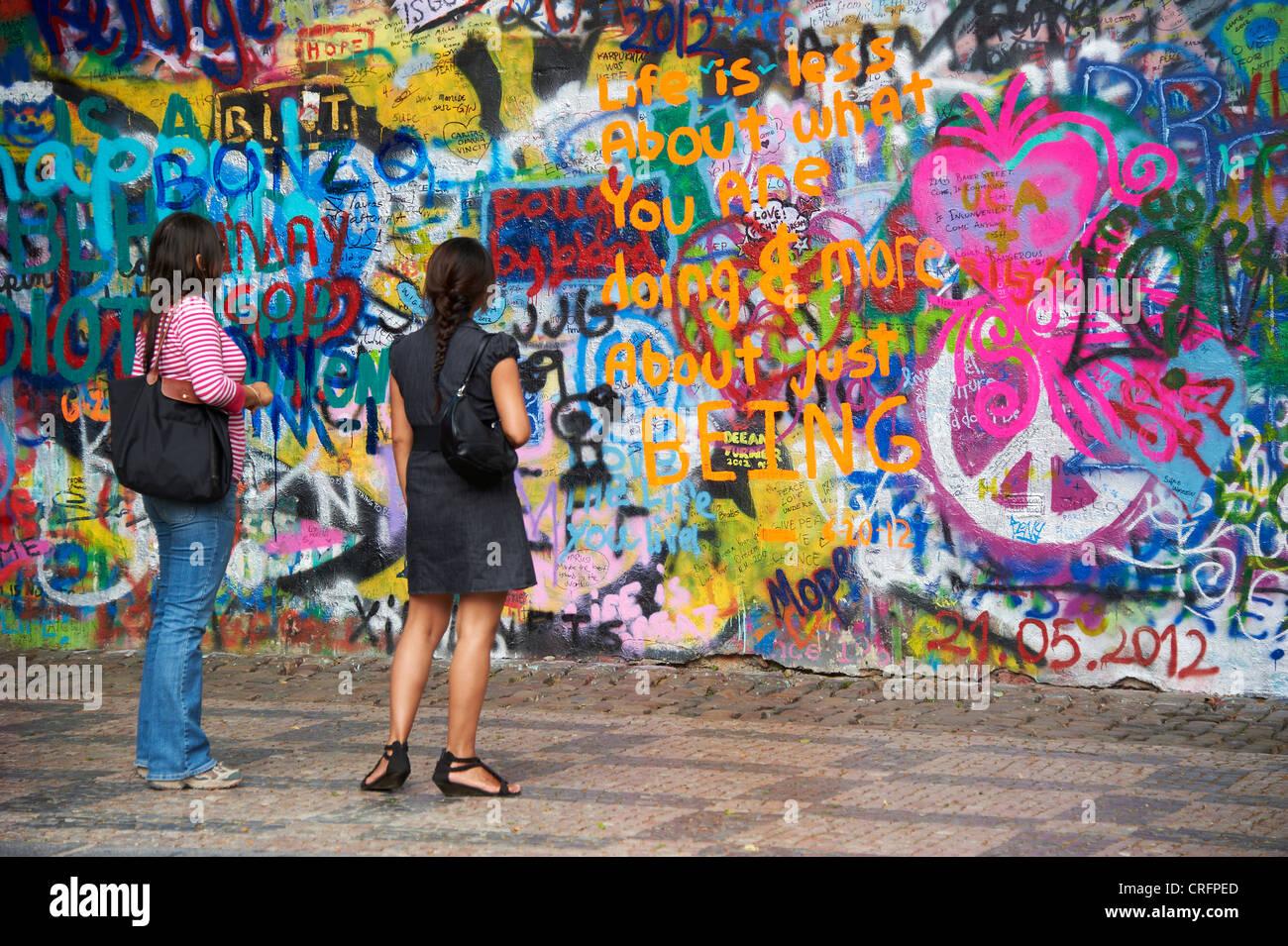 The John Lennon graffiti Wall in Prague, Czech Republic, tourists womans looking - Stock Image