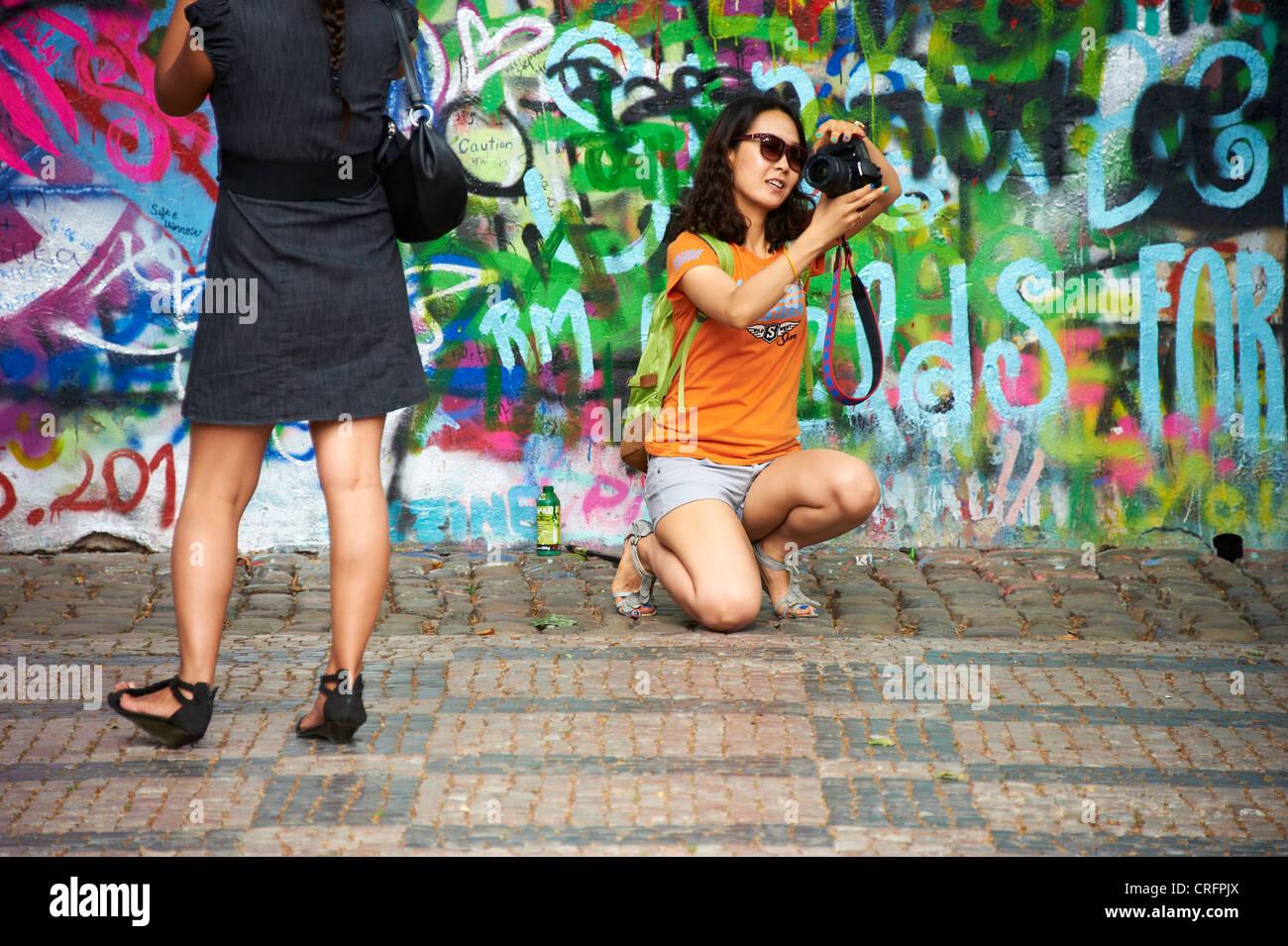 The John Lennon graffiti Wall in Prague, Czech Republic, tourist woman take a self photo - Stock Image