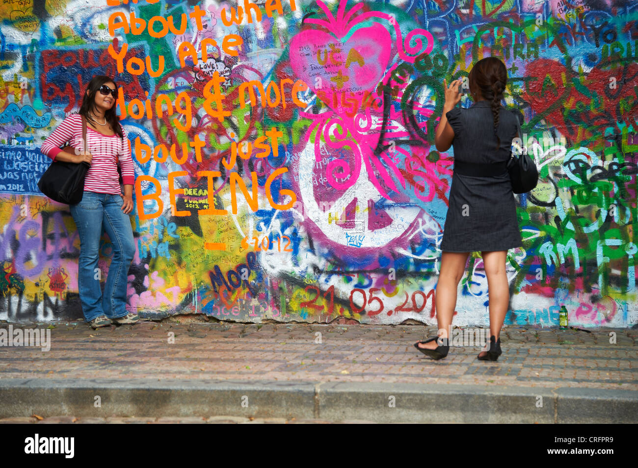 The John Lennon graffiti Wall in Prague, Czech Republic, tourists womans - Stock Image