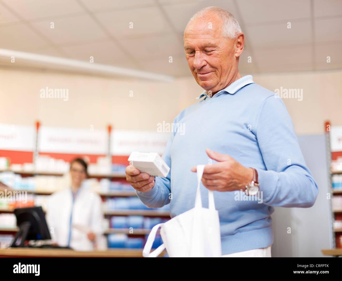 Man picking up prescription at pharmacy Stock Photo