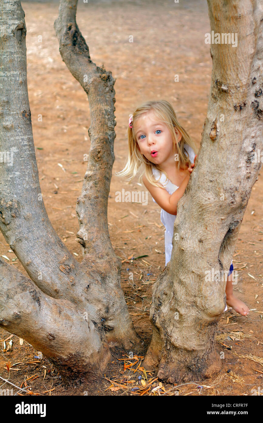 Girl playing in tree in park - Stock Image