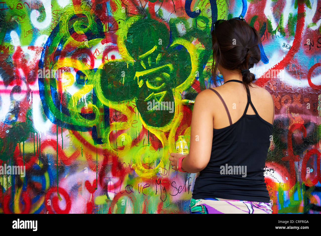 The John Lennon graffiti Wall in Prague, Czech Republic, tourist woman painting and writing testament - Stock Image