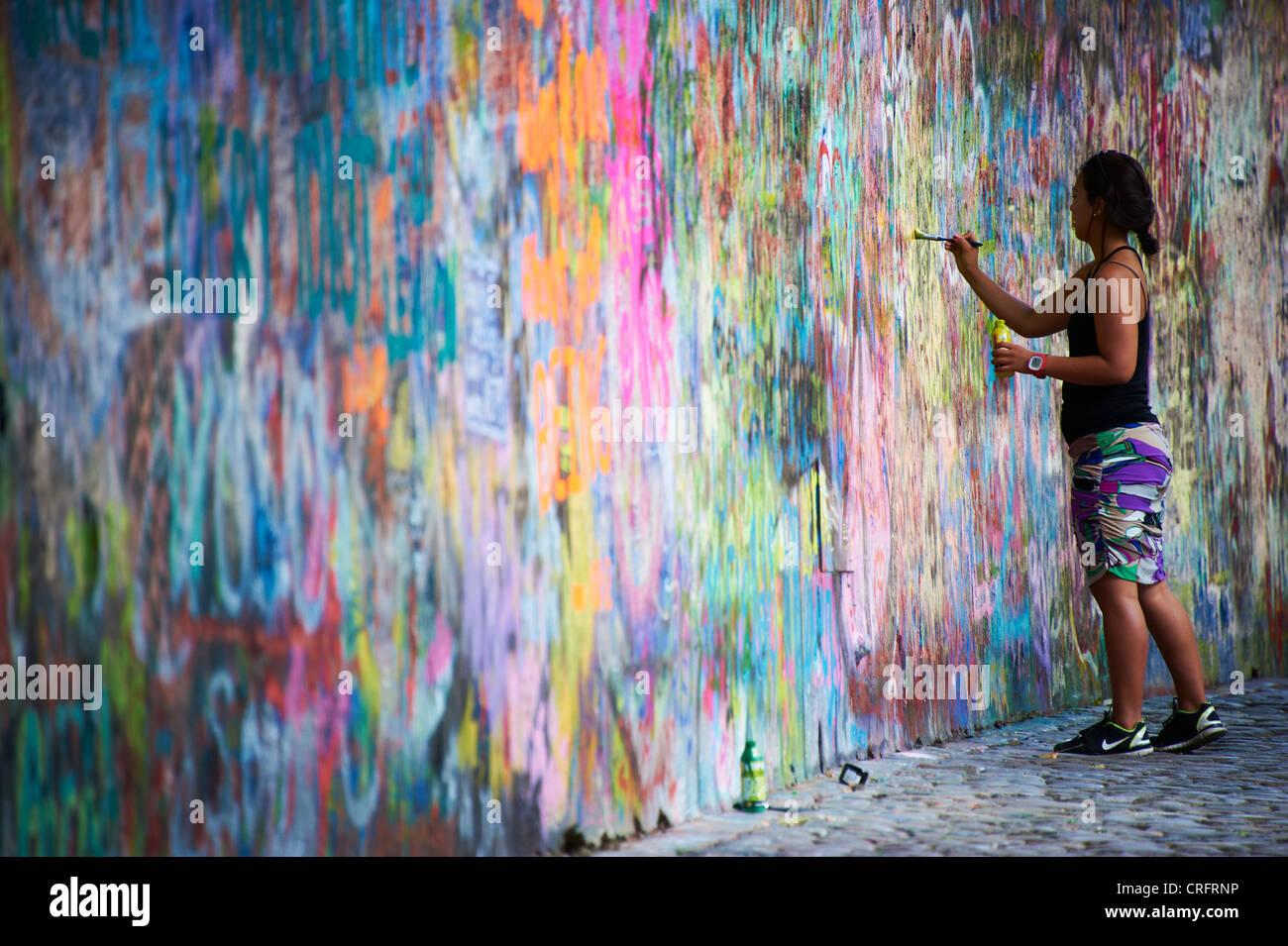 The John Lennon graffiti Wall in Prague, Czech Republic, tourist woman painting and writing testament - Stock Image