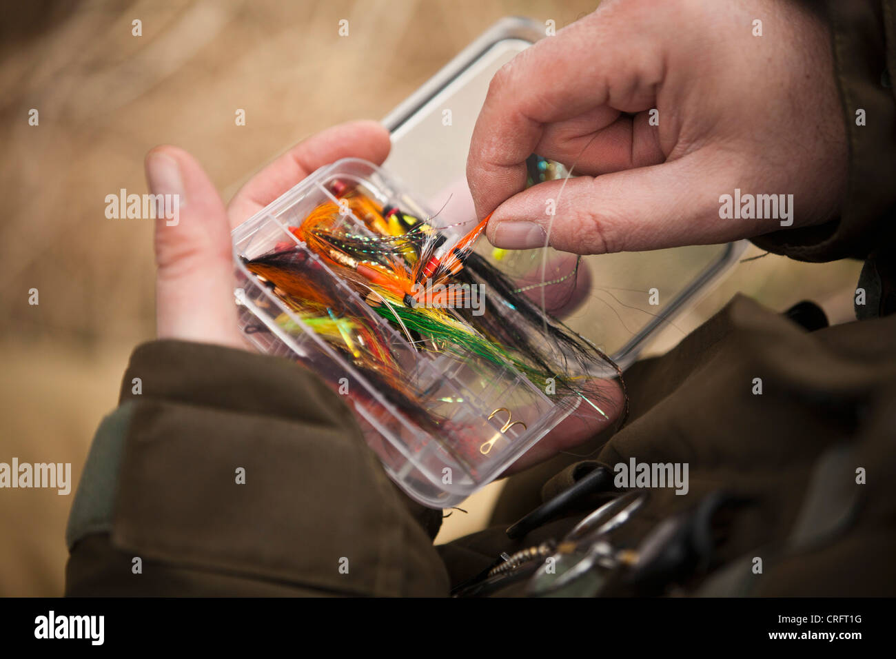 Man pulling fishing tackle from box - Stock Image