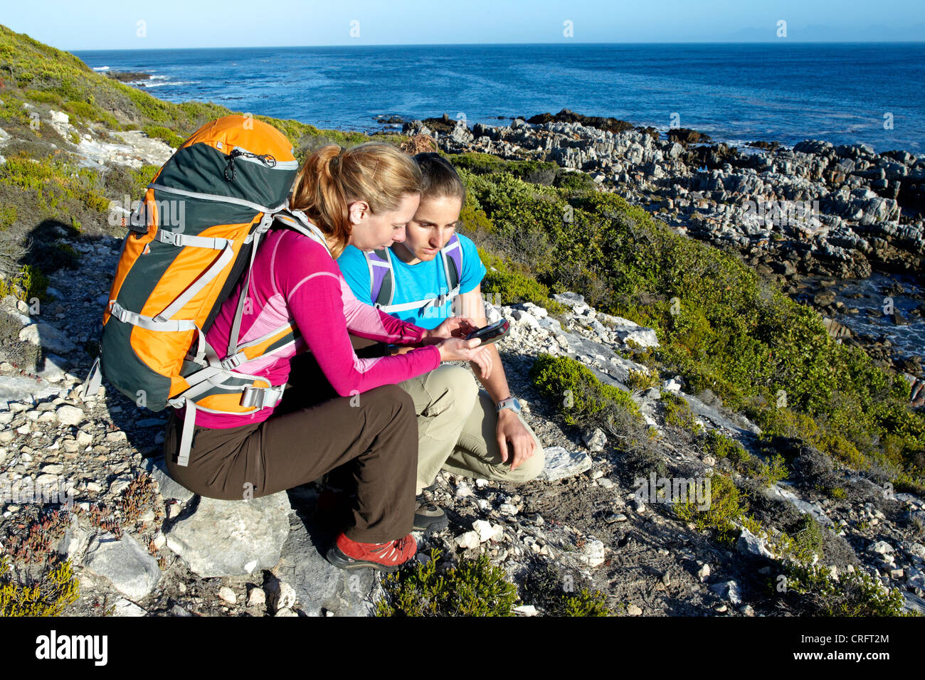 Two women checking a GPS device while hiking on an ocean trail between Gansbaai and De Kelders. South Africa. - Stock Image