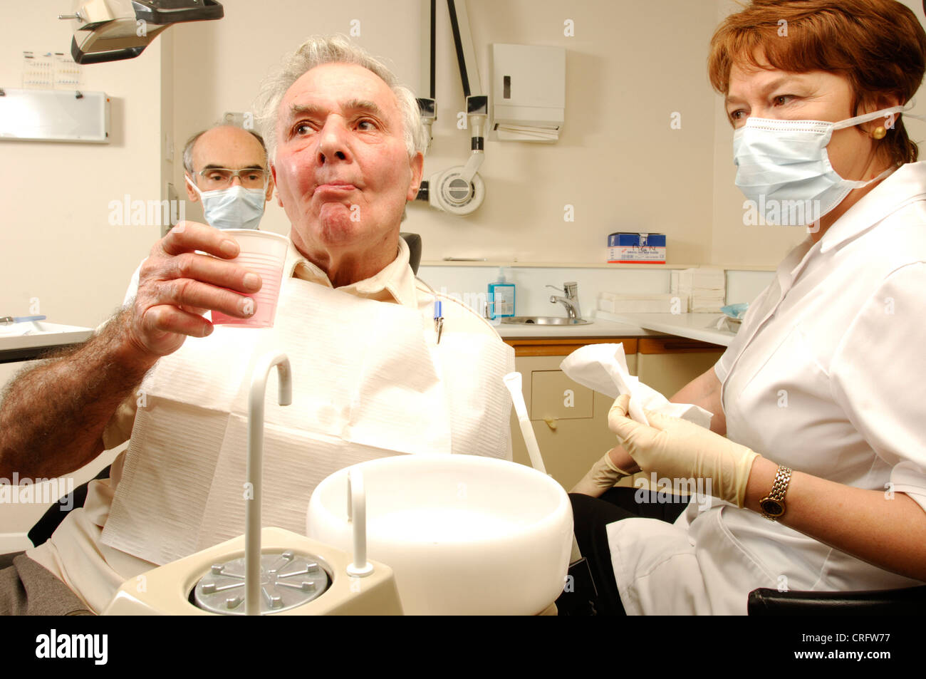 An elderly man rinses with anti-microbial mouth wash after dental treatment, watched by the dentist's assistant - Stock Image