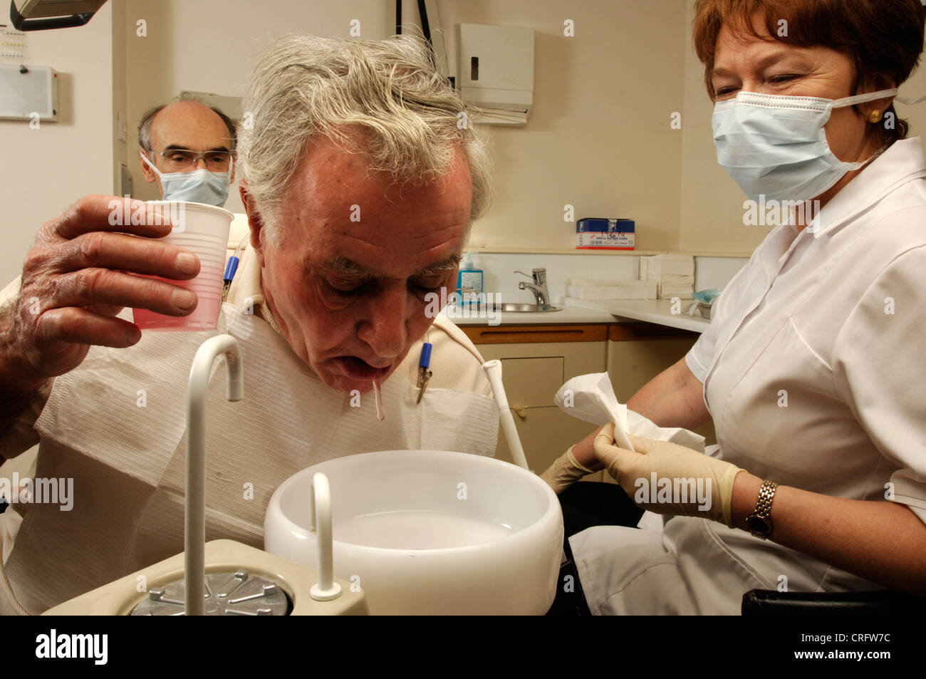 An elderly man rinsing his mouth out with anti-microbial solution, watched by the dentist and his assistant. - Stock Image