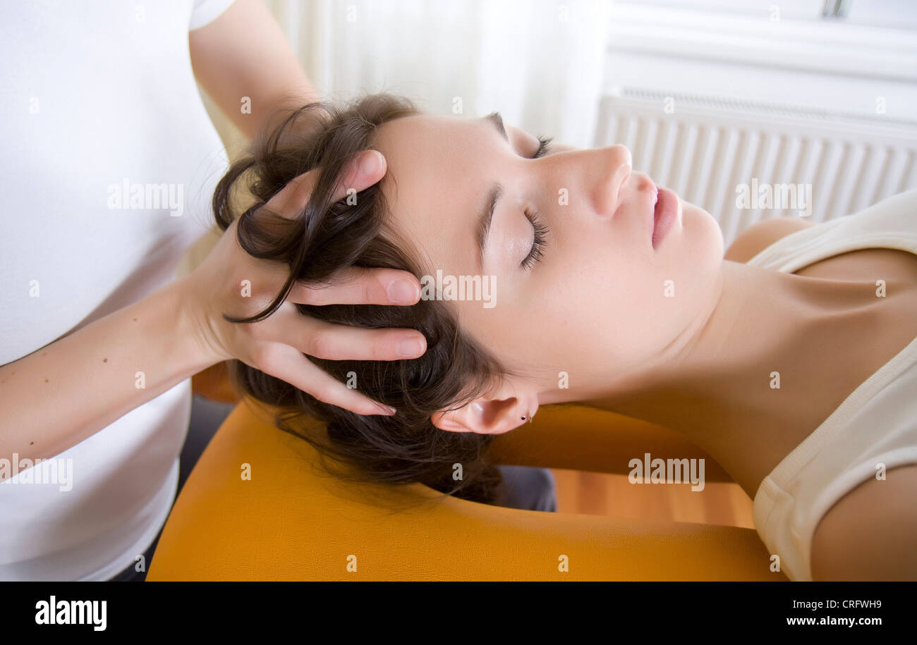physio therapy: therapist relaxes tensions of neck muscles - Stock Image
