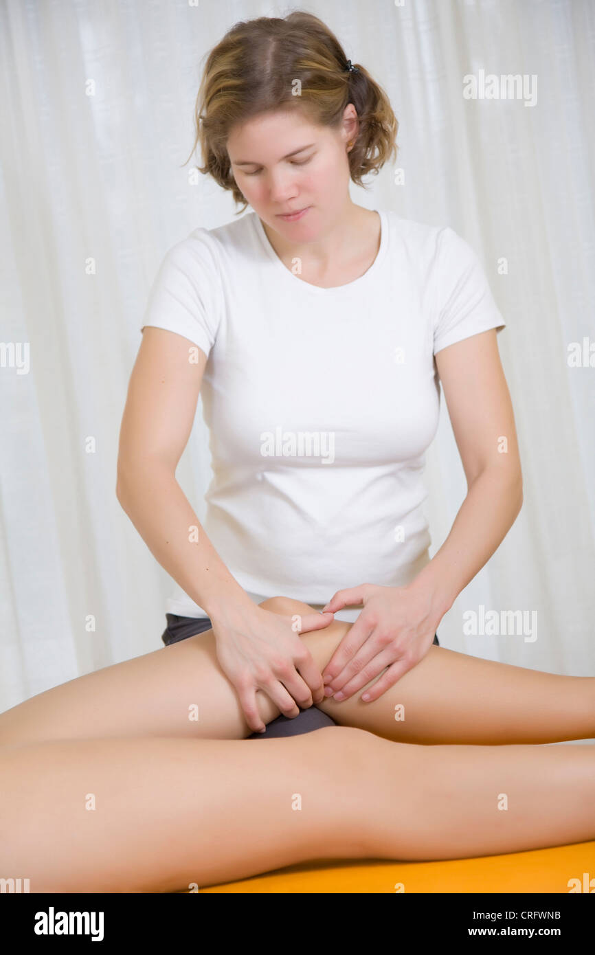 physio therapy: therapist relaxes tensions of leg muscles - Stock Image