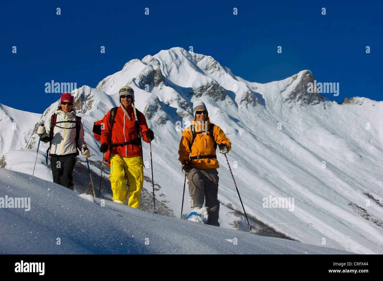 three persons on snow shoes, walking in deep powder snow in the North of Alps near Les Menuires ski resort, France, Stock Photo