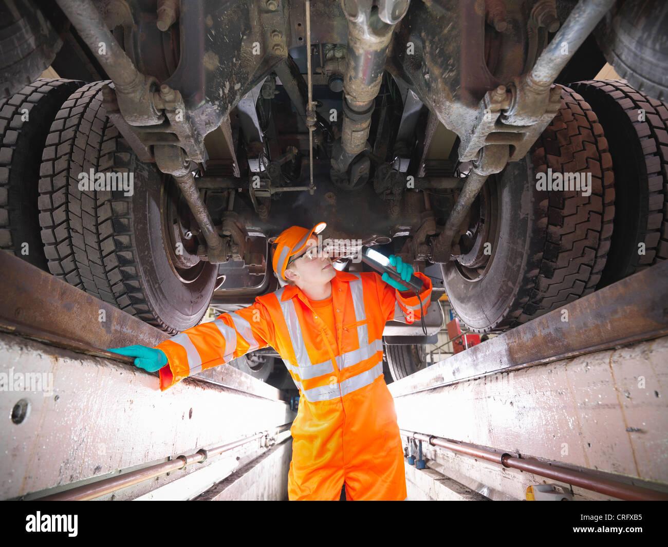 Apprentice engineer examining engine - Stock Image