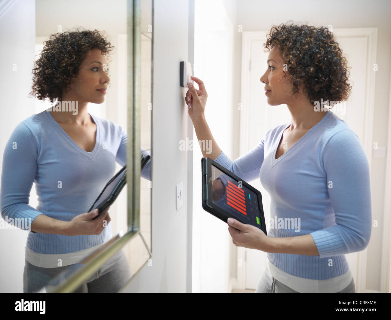 Woman adjusting thermostat in home - Stock Image