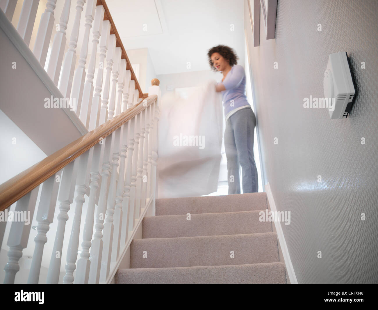 Woman shaking out sheets on staircase - Stock Image