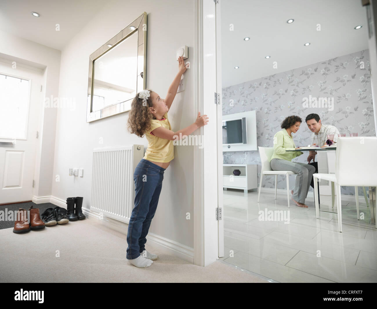 Girl reaching for thermostat - Stock Image