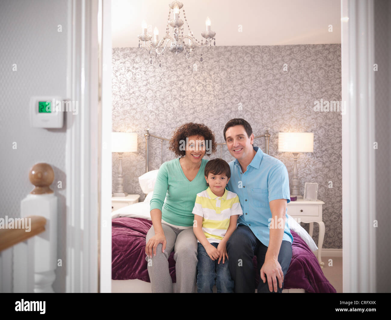Family smiling together in bedroom - Stock Image