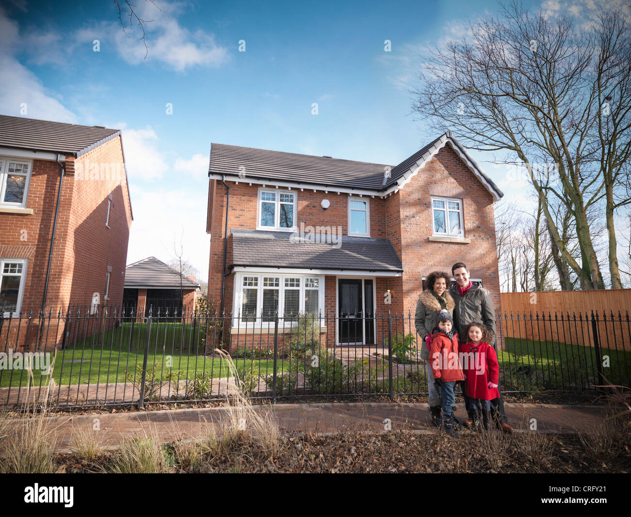 Family smiling outside house - Stock Image
