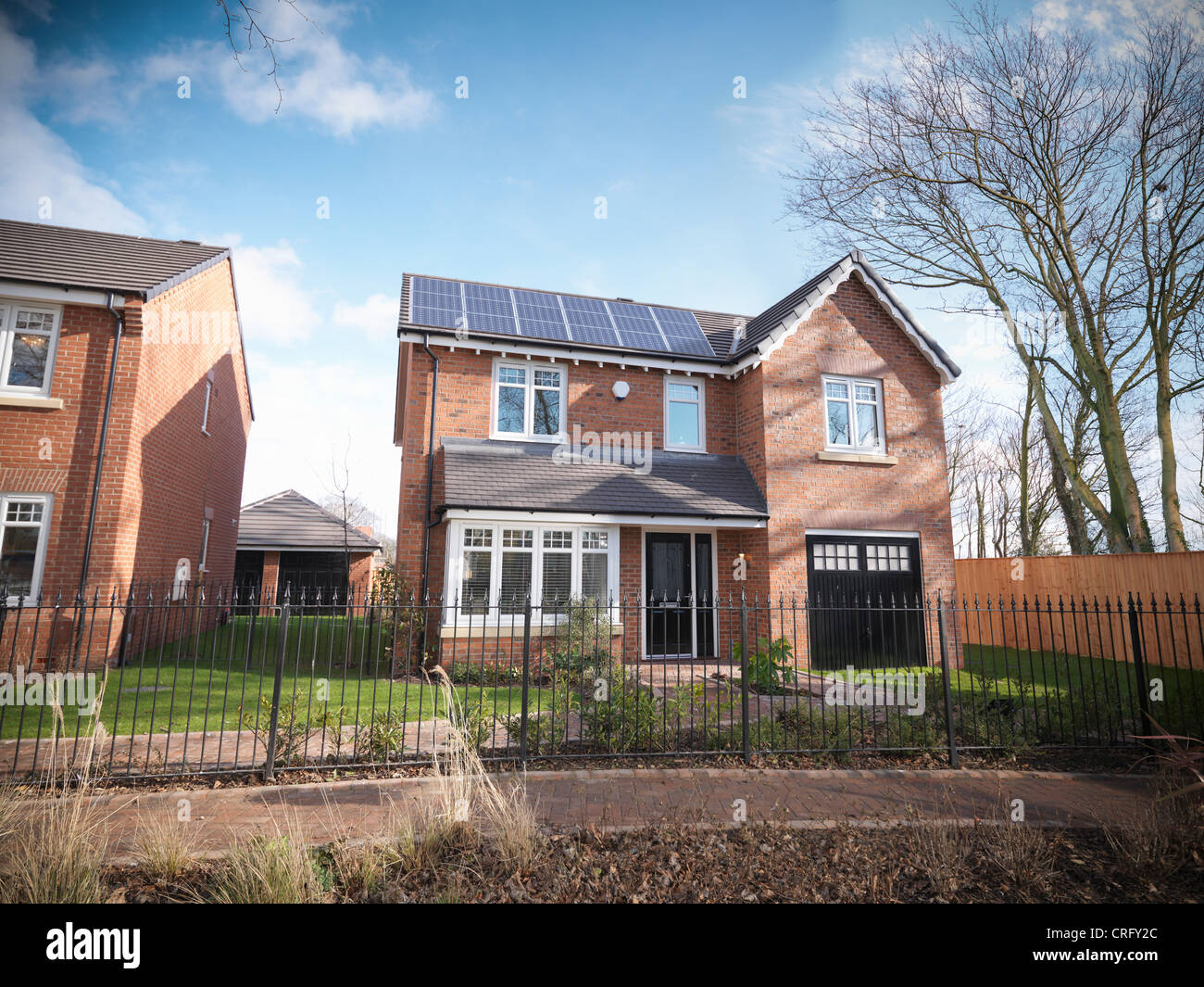Brick house behind iron gate - Stock Image
