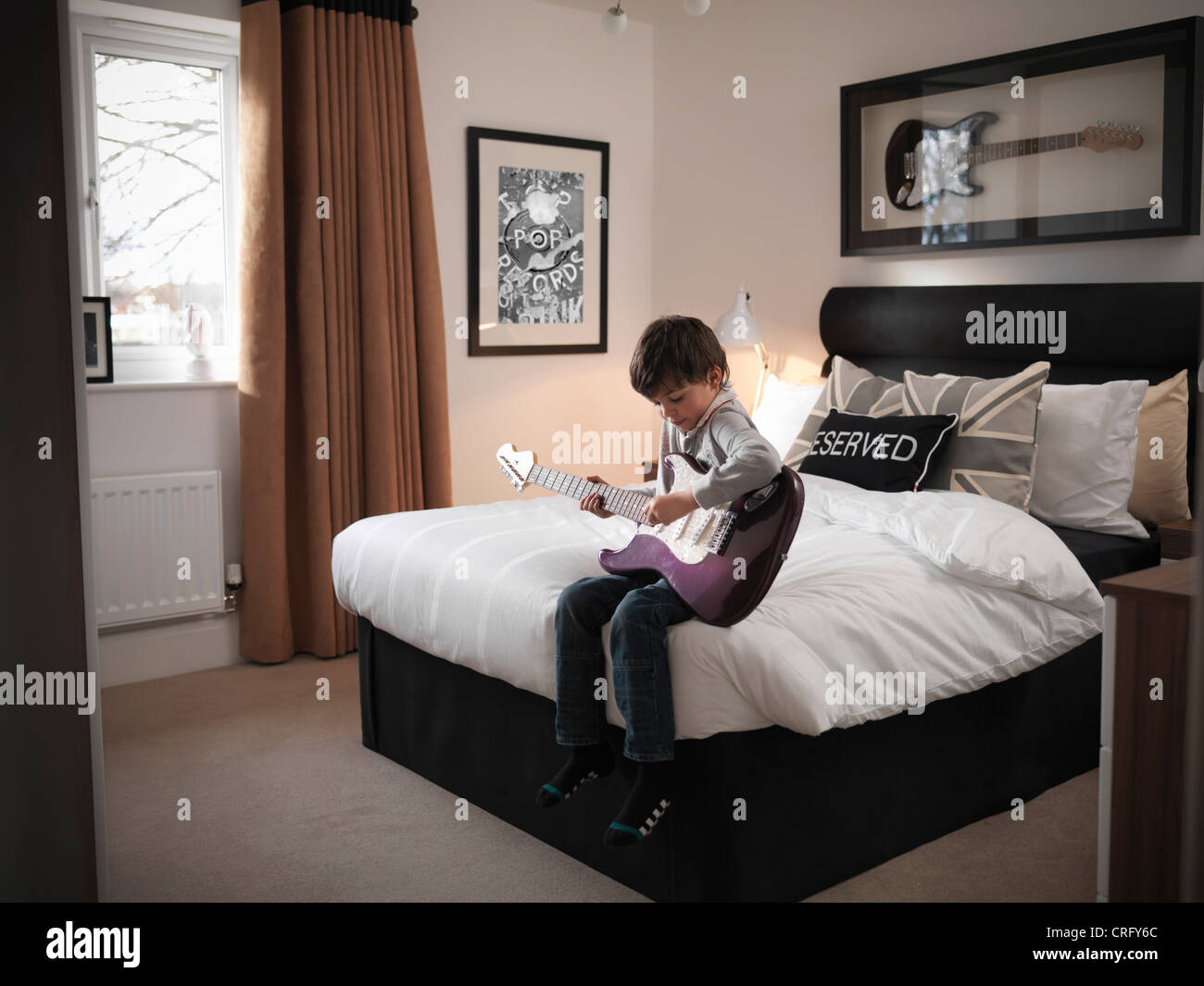 Boy playing guitar in bedroom - Stock Image