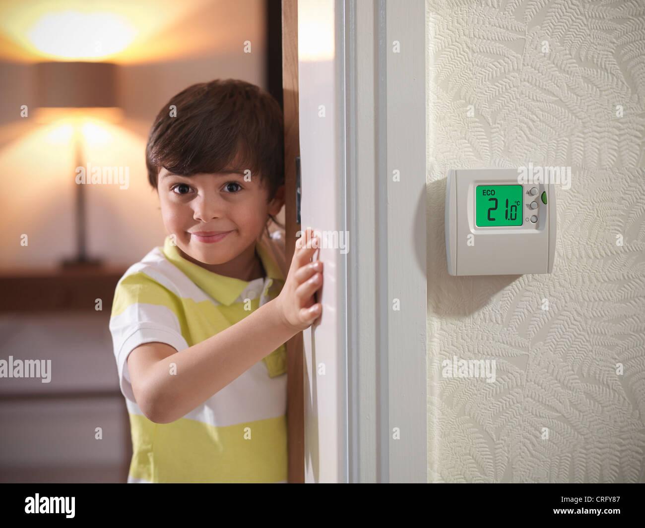 Boy peeking around doorway - Stock Image