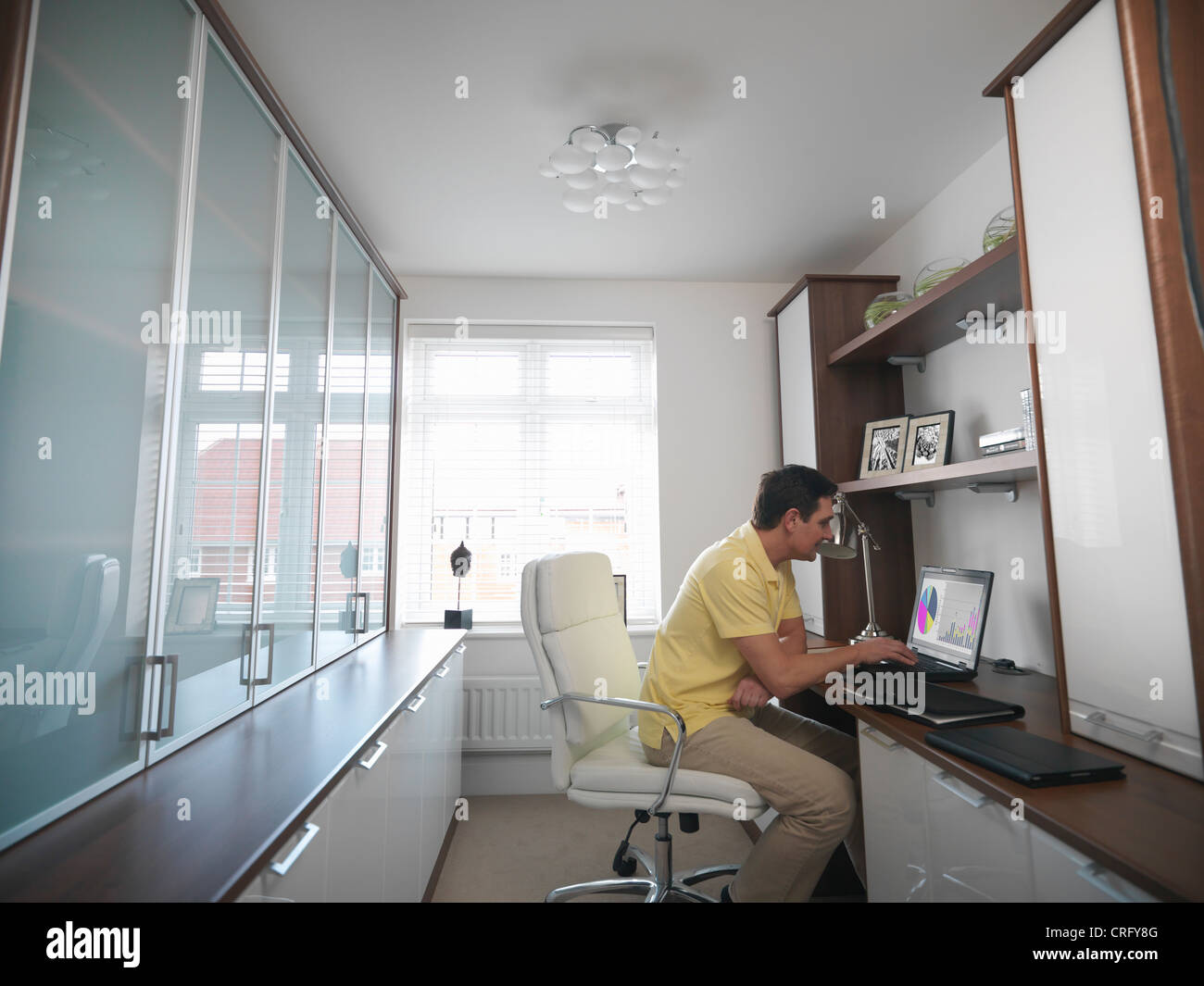 Man working on laptop in home office - Stock Image