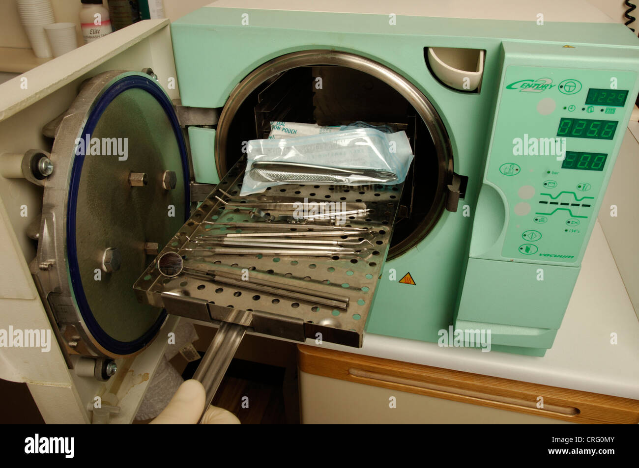 A gloved hand inserts used dental tools into an autoclave to be sterilized by high pressure steam. - Stock Image
